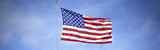This is a shot of an American flag on a flagpole, waving in the wind against a blue sky. - 90022301
