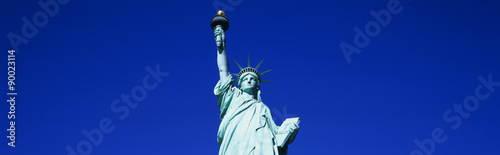 This is the top half of the Statue of Liberty against a blue sky in horizontal format. - 90023114