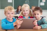 Fototapety drei kinder in der grundschule mit tablet-pc