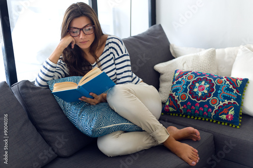 Beautiful young woman reading a book on the sofa.