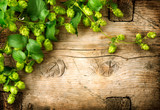 Fototapety Hop twig over old wooden table background. Vintage style. Beer production. Brewery