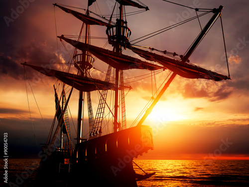 Fotobehang Schip Old ancient pirate ship on peaceful ocean at sunset.