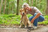 Fototapety Frau mit Labrador Retriever im Wald