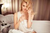 Beautiful blonde drinks champagne