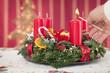 Adventskranz am ersten Advent mit einer brennenden Kerze