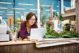 Fototapety Florist Using Laptop In Flower Shop