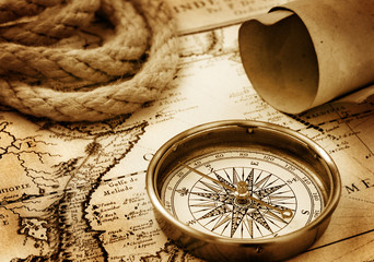 Vintage compass, rope and paper sroll on map