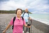 Fototapety happy senior couple hiking on the coast beach