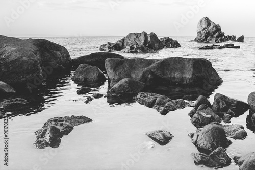 dramatic black and white rocks protruding from the sea