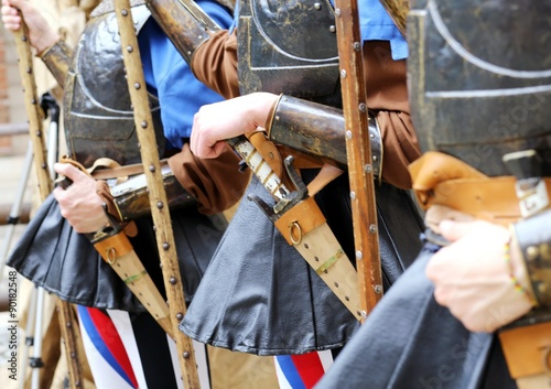 Poster medieval soldiers with hands on the sheath knife