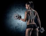 Fototapety Muscular woman in studio on dark background