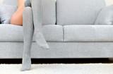 Woman with beautiful legs sitting on sofa.