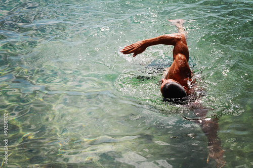 Poster, Tablou Strong muscular man swimming in the sea ocean scrawl style