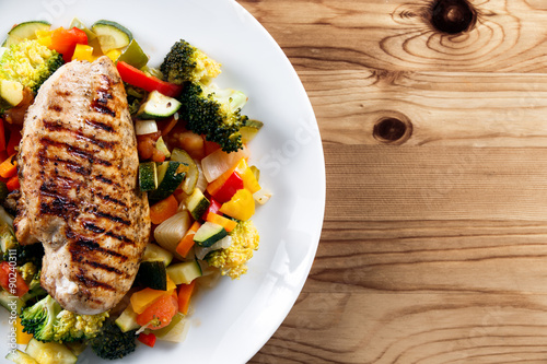 obraz PCV Grilled chicken fillet, breast with cooked vegetable Tomatoes, Carrots, Peppers, Courgettes, brocoli on plates.