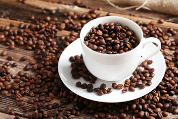 Coffee beans in cup on a brown wooden background