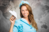 Air hostess holding a paper plane against world map