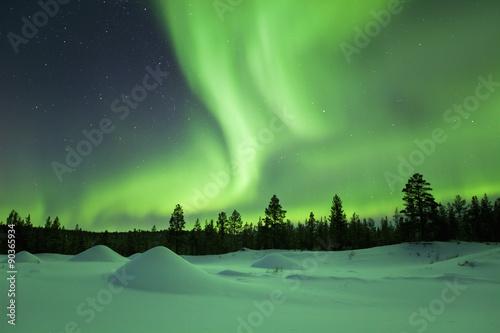 Canvas Noorderlicht Aurora borealis over snowy winter landscape, Finnish Lapland