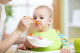 Fototapety Mother feeding baby with spoon