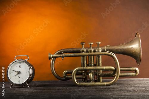 mata magnetyczna Tromba in ottone con sveglia su piano di legno e sfondo arancio