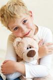 Fototapety Cute little boy hugs his teddy bear