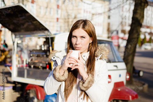 Foto op Canvas Chocolade Girl wearing coat holding cup with drink near street food.
