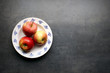 Fresh apples on plate with copyspace on grey kitchen table