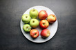 Fresh apples on big white plate and grey kitchen table background