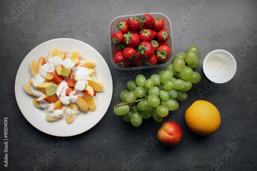 Fresh fruit snack with yoghurt on kitchen table - healthy eating background