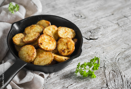 baked potatoes in the pan on a light wooden surface