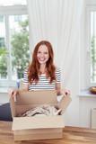 zufriedene kundin öffnet zuhause ein paket - 90536549