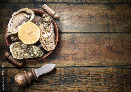 Poster Raw oysters on the old wooden table.
