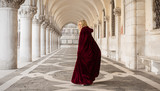 Mysterious woman in red cloak walking away