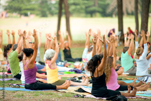 people doing yoga in a park at sunset
