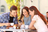 Fototapety Friends watching media in a smart phone in a coffee shop