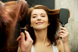 Brunette woman brushing her hair.