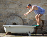 Fototapety man in retro swimsuit jumps to the outdoor bathtub