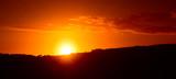 Sole che sta tramontando dietro una collina