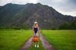Постер, плакат: девушка стоит на дороге с чемоданом