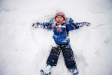 Fototapety Adorable little boy in blue jacket, red hat and scarf,  lying on