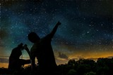 Silhouette of adult man observes night sky with child. - Fine Art prints