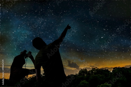 Silhouette of adult man observes night sky with child. - 90652511