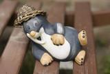 Ceramic garden ornament lying mole with straw hat
