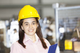 Mechanical engineer standing with a clipboard at metallurgy fact poster