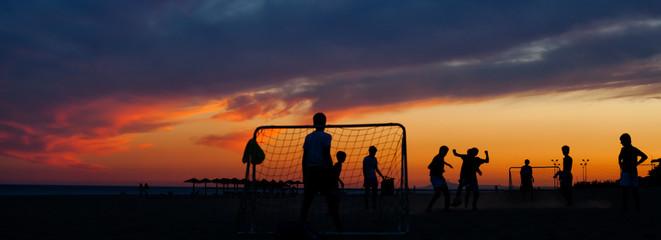 Chicos jugando el fútbol al atardecer en la playa © davidfpinilla