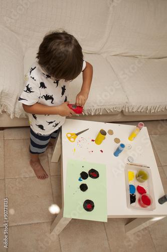 Niño pintando en casa con témperas de colores © lorenphotography