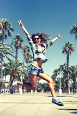 Beautiful young crazy happy girl is jumping in palm trees in summer in Barcelona wearing sunglasses blue jeans shirts