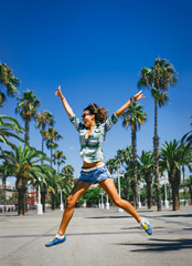 Young beautiful crazy girl is jumping and having fun around the palm trees in sunny Barcelona