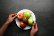 Hands holding white plate with fruits on table