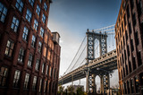 Fototapety Manhattan bridge seen from a narrow alley enclosed by two brick buildings on a sunny day in summer