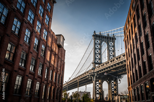 Foto Murales Manhattan bridge seen from a narrow alley enclosed by two brick buildings on a sunny day in summer